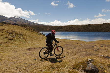 Cyclist reaching lagoon Santo Domingo, Cotopaxi National Park
