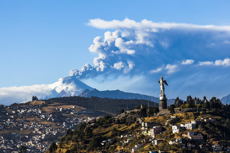 Cotopaxi volcano eruption and Panecillo's Madona seen from Quito, Ecuador