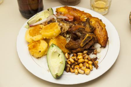 ecuadorian: Dinner plate with fried pork, potato pancakes, banana and avocado