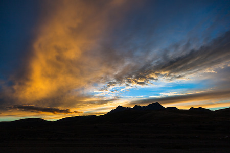 Beautiful sunset with gold, blue clouds, and oranges, Sunset at the Cotopaxi National Park, with the silhouette of Rumi? ahui volcano Stock Photo