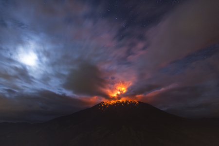QUITO, ECUADOR - March 4, 2016: Tungurahua Volcano is one of the most active of Ecuador, you can see an explosion at 4 am with the moon shining through the clouds. Editorial