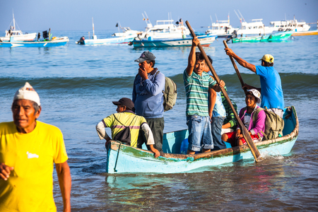 concluding: Puerto Lopez, Ecuador, June 30, 2015: Unidentified people disembarking the beach from the fishing boats after concluding his day