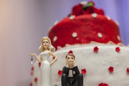 topper: Figurines on bottom of red and white wedding cake Stock Photo