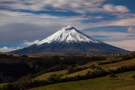 Cotopaxi volcano illuminated by moonlight with cultivated fields in the foreground