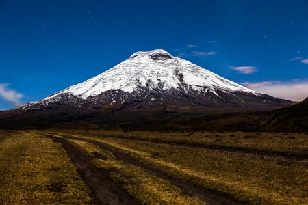 artificially: Cotopaxi volcano trails in the foreground illuminated by moonlight Stock Photo