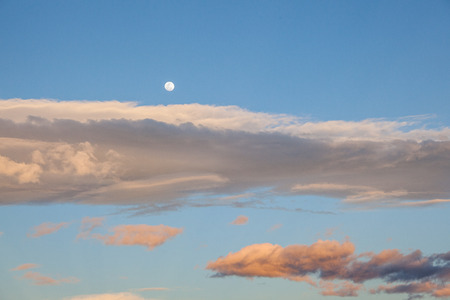 apparently: Almost full moon appears early in the afternoon apparently over clouds Stock Photo