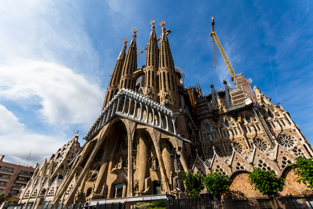 BARCELONA, SPAIN, June 8, 2017: Southwest view of the Sagrada Familia from Sardenya Street, lit by the afternoon sun. Editorial