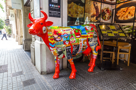 BARCELON, SPAIN, JUN 8, 2017: A cow painted red and commercials, catches the attention of customers of the restaurant Purabrasa.