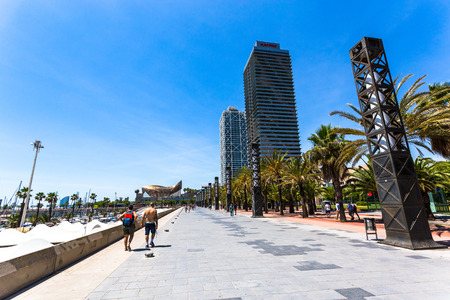 BARCELONA, SPAIN, JUNE 6, 2017: Neighbors and tourists of Barcelona stroll along the promenade of the Olympic Port of Barcelona one summer morning.