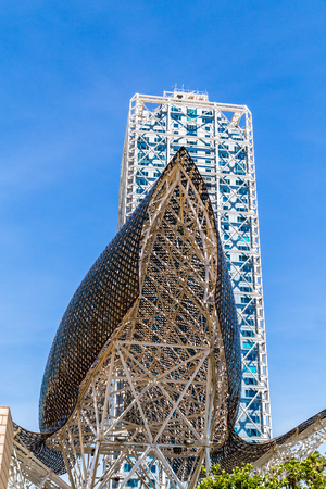 BARCELONA, SPAIN, JUNE 6, 2017: Monument El Pez Dorado in the Olympic port of Barcelona almost at the foot of the MAPFRE building and Arts Hotel, can be seen from the beach La Barceloneta