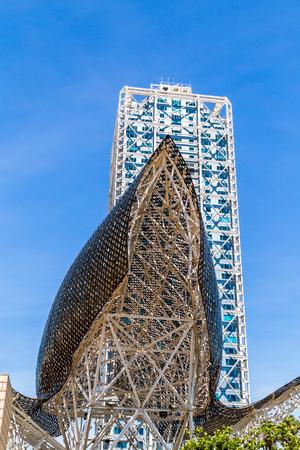BARCELONA, SPANJE, 6 JUNI 2017: Monument El Pez Dorado in de Olympische haven van Barcelona bijna aan de voet van het MAPFRE-gebouw en Arts Hotel, kan worden gezien vanaf het strand La Barceloneta