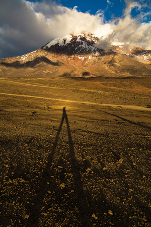 Elongated shadow of the photographer is projected towards the Chimborazo volcano