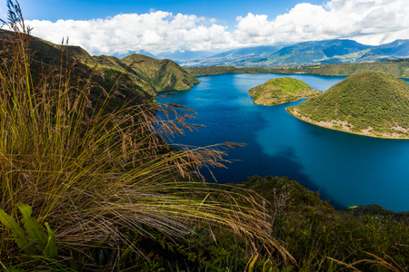 Cuicocha, beautiful blue lagoon in the interior of the Cotacachi volcano crater with spikes of grass in the foreground