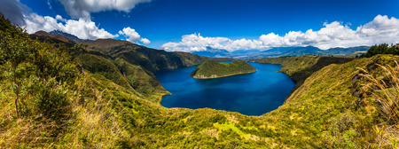 Panoramic of Cuicocha, beautiful blue lagoon inside the crater of the Cotacachi volcano on the left