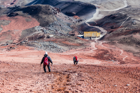 Climber descending the red sand towards the refuge of Cotopaxi