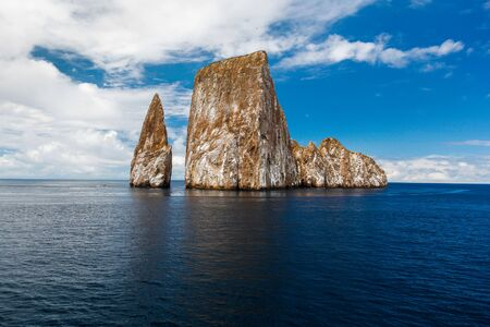 Sharp rock or islet called Lion Asleep, near the coast of San Cristobal Island, Galapagos Фото со стока