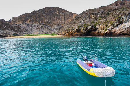 Rubber boat with motor ready to take tourists in Punta Pitt, Galapagos Stock Photo