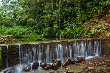 Small artificial waterfall in a beautiful river surrounded by jungle vegetation