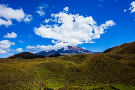 Cotopaxi National Park, the volcano crowned by white clouds and the paramo at its feet. Stock fotó