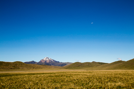 Blue sky with small moon and Andean mountains at the base Banco de Imagens