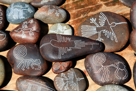 Souvenirs of Nazca lines carved into small rounded stones