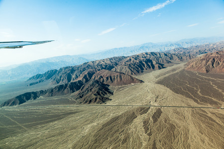 View from the window of an airplane of the relief of the desert and the lines that are formed by erosion in rainy seasons in the plateau of Nazca, Peru
