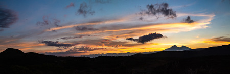 Panorama Sunset with orange clouds, blue sky, mountain silhouette, and Andean paramo Banco de Imagens