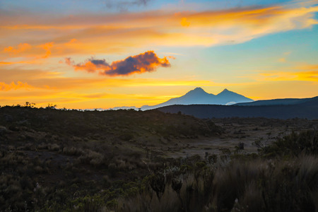 Sunset with golden and orange clouds, blue sky, mountain silhouette, and Andean paramo