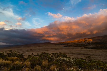 Sunset with orange clouds, blue sky, mountain silhouette, and Andean paramo