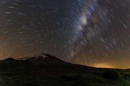 Long exposure, the milky way with the silhouette of the Chimborazo volcano at the foot Фото со стока