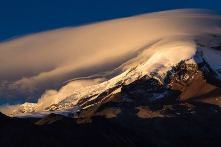 Semi-covered Chimborazo with clouds and blue sky, receiving the first rays of sun