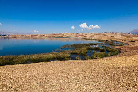 Huaypo lagoon with a beautiful blue sky and dry summer fields
