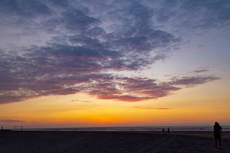 Beautiful sunset with clouds of various colors on the dark beach Фото со стока