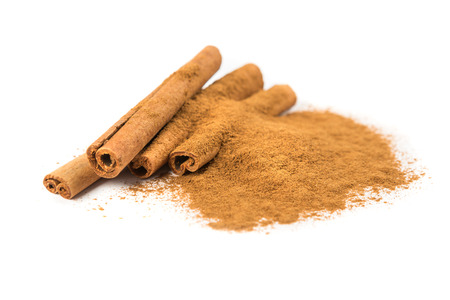 enhancer: Stack of cinnamon sticks and ground cinnamon isolated on white background