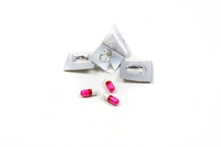 Opened pink and white pills isolated on white background