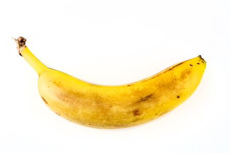 bedraggled: One old yellow banana isolated on white background