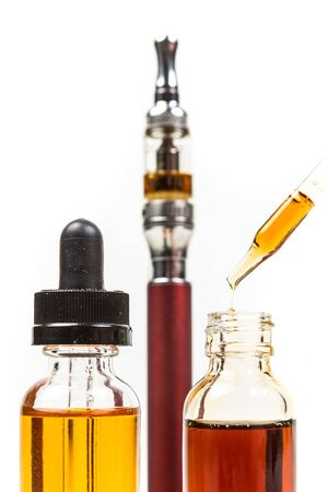 Assorted flavors vape juice and eyedropper being used isolated on white background