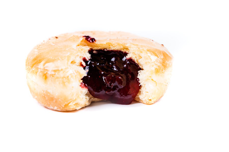 filled out: A frosted jelly filled donut with a bite out of it isolated on a white background