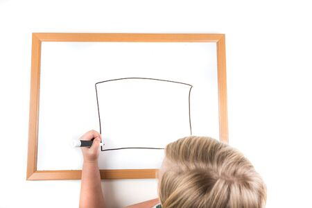dry erase board: Young girl drawing on a dry erase board with a marker