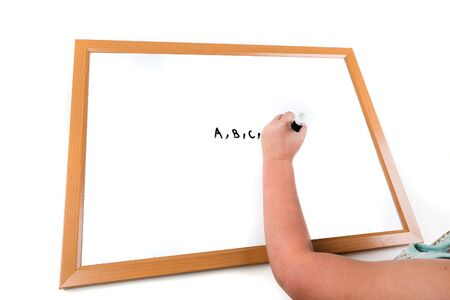 Child writing on a dry erase board with a marker