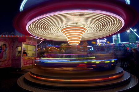 Carousel in neon light on a fairground at Karlsruhe at night