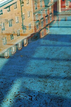 Old houses in Lisbon mirrored in the puddle