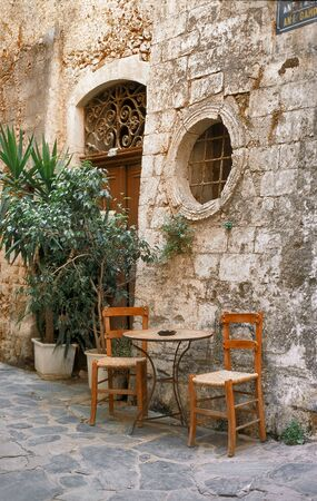 Two old chairs in front of entrance in Crete