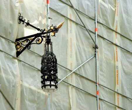 Tuebingen, Germany: Shield of a restaurant breaks through protective tarpaulin in the scaffolding Фото со стока