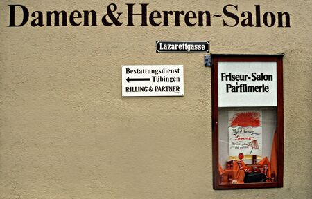 Tübingen, Germany: Hairdressing salon with signs on the wall: hospital alley and burial institute
