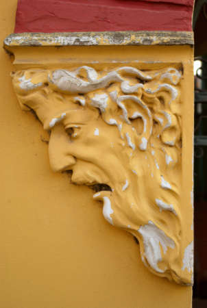 A yellow face with mouth open in astonishment is a decorative detail on an apartment building Stock fotó