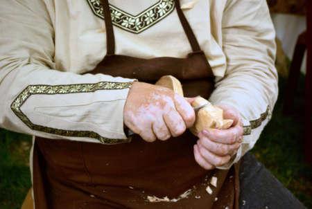 trinchante: H�ngaro tallador de madera en traje folcl�rico crear una cuchara con cabeza de caballo manejar