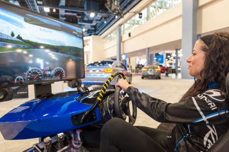 Miami Beach, FL, EE.UU. - 6 de noviembre de 2015: modelo de rayos conducir el simulador de carreras de Hyundai durante el Auto Show Internacional de Miami 2015 en el Centro de Convenciones de Miami Beach, en el centro de Miami Beach.