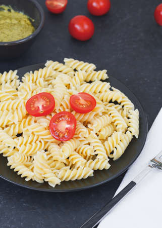 Italian pasta with tomatoes on the black plate