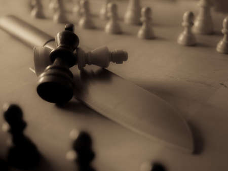 Chess pieces and kitchen knife. Strategy game. It is played on a 64 square black and white board.